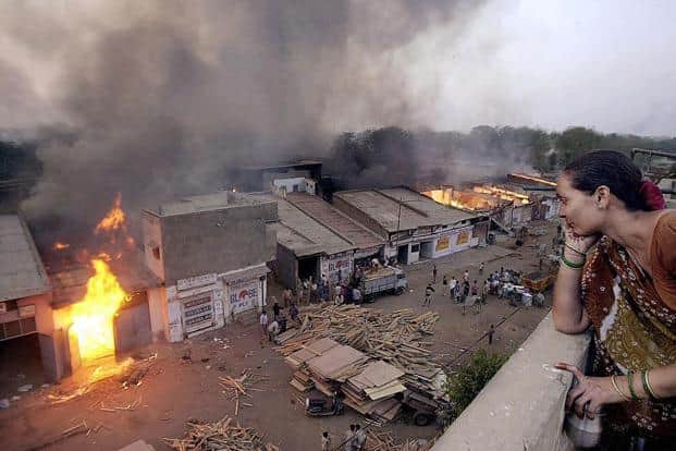 A 2002 photo of an Ahmedabad resident watching a wood market burn during riots in the city. The Gulberg Society case is one of the nine cases of the 2002 Gujarat riots probed by the Supreme Court appointed SIT. Photo: AFP