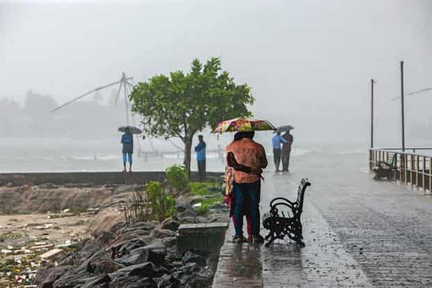 People at the Fort Kochi beach taking cover from the heavy rain on Tuesday. Roshan Mohammad/Mint