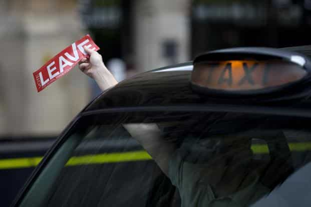 "A taxi driver holds a sticker for the ""Vote Leave"" pro-Brexit campaign as he drives past media in central London. Photo: Justin Tallis/AFP"