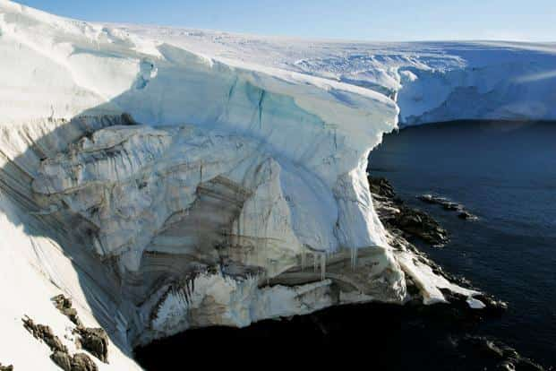 Melting ice shows through at a cliff face at Landsend, on the coast of Cape Denison, Antarctica. Photo: Reuters