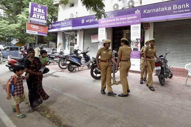 Police personnel guard a branch of Karnataka Bank in Chennai. Photo: PTI