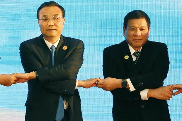 A file photo of Chinese Prime Minister Li Keqiang (left) and Philippine President Rodrigo Duterte link arms during the ASEAN Plus Three summit in  Vientiane, Laos. Photo: AP
