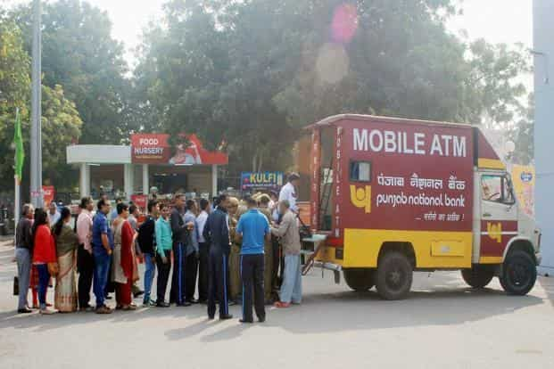 A mobile ATM is operated out of a vehicle—usually a bus or van—and the machine is accompanied by a person who hands over cash to customers. Photo: PTI