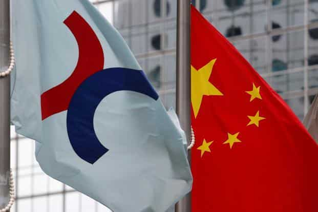 A Hong Kong Exchanges flag (left) is hoisted beside a Chinese national flag outside the Hong Kong Stock Exchange in Hong Kong. Photo: Reuters