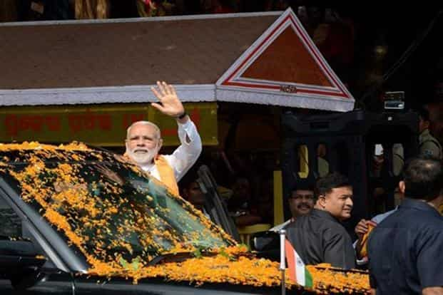 Prime Minister Narendra Modi waves to people during his visit to Lingaraj temple after darshan of Lord Lingaraj in Bhubaneswar on Sunday. Photo: PTI