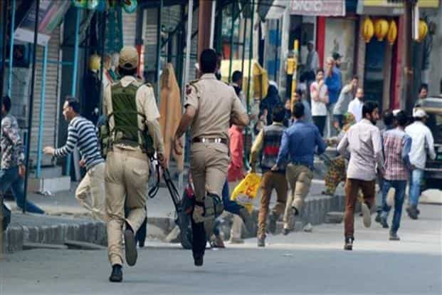 Security personnel chase away agitators during a protest against the police action on protesters in Kupwara on Friday. File photo: PTI