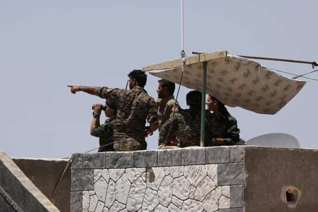 A file photo. Syrian Democratic Forces (SDF) fighters stand atop of a building near Raqqa city, Syria. Photo: Reuters
