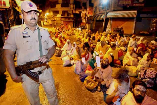 A securityman stands guard as sadhus wait to board a bus for the yatra. PTI