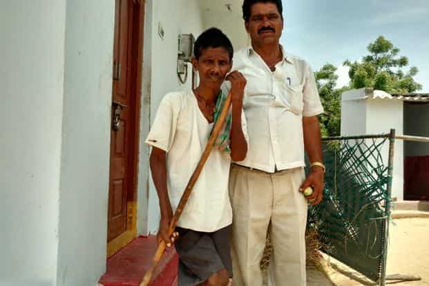 Yadaiah (left), a resident of M. Edavalli village who has deformed knees due to fluorosis, stands in front of his house with sarpanch Bokka Bhupal Reddy. Photo: Yunus Y. Lasania