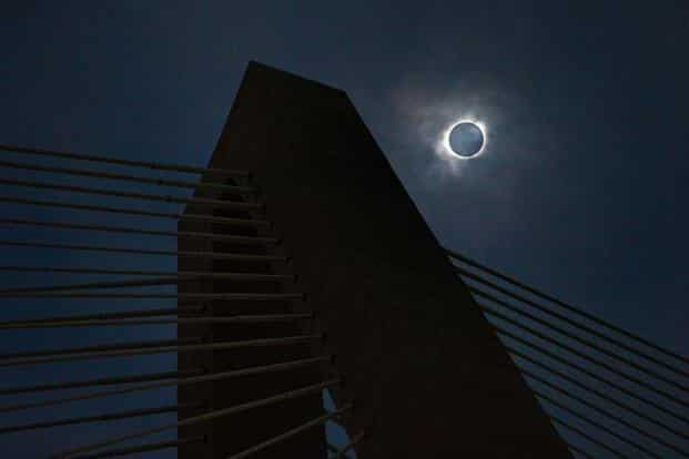 A solar eclipse seen through a layer of clouds over the Ravenel Bridge in Charleston, South Carolina, the last point in the path of totality. AP