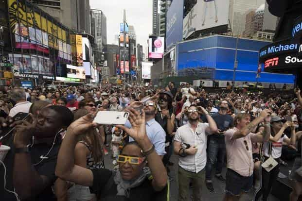 People in Times Square try to takes photos and view the solar eclipse in New York. AFP