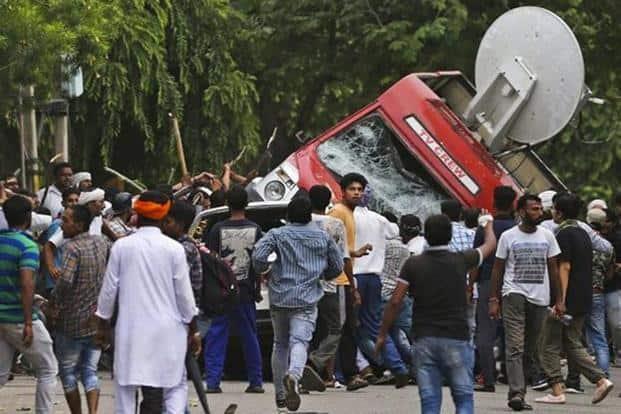 Followers of Dera Sacha Sauda chief Gurmeet Ram Rahim Singh overturn an OB van on the streets of Panchkula in Haryana on Friday. Photo: AP