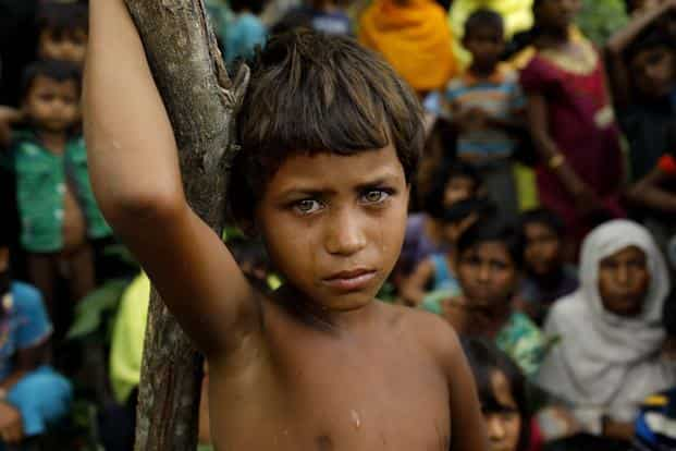 A Rohingya refugee girl and newly arrived refugees who fled to Bangladesh from Myanmar in Ukhiya on Wednesday. Myanmar's state counsellor Aung San Suu Kyi appears to hold the majoritarian view that Rohingyas are not citizens of Myanmar. Photo: AFP