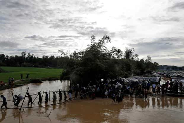 Rohingya Muslims cross a swollen river at a refugee camp in Cox's Bazar, Bangladesh, on 17 September. Photo: Reuters