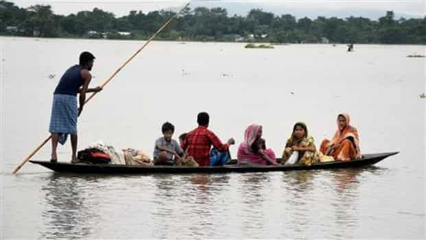 Villagers shift from a flood-hit area in Bolbola in Goalpara, Assam, on Sunday. Photo: PTI