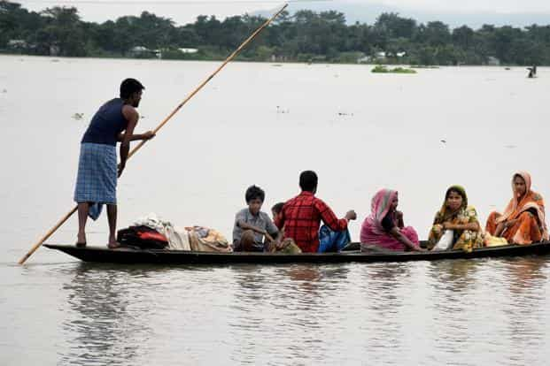 Villagers shift from a flood-hit area at Bolbola in Goalpara, Assam, on Sunday. Photo: PTI