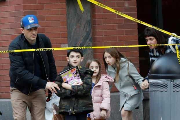 Parents pick up their children from a school near the attack site in New York City on Tuesday. Reuters