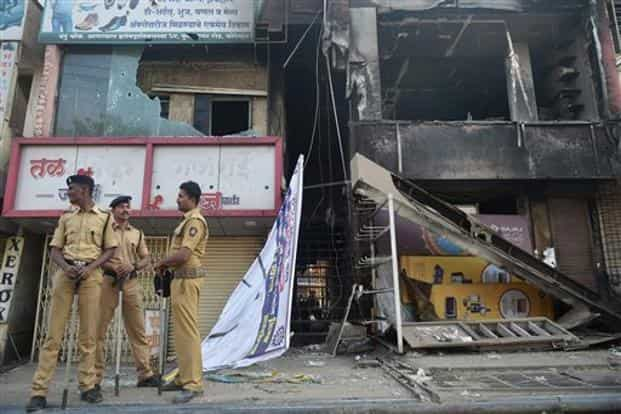Police guard near charred and vandalized shops following the violence during celebrations of 200th anniversary of the Battle of Bhima-Koregaon, on Tuesday. Photo: PTI