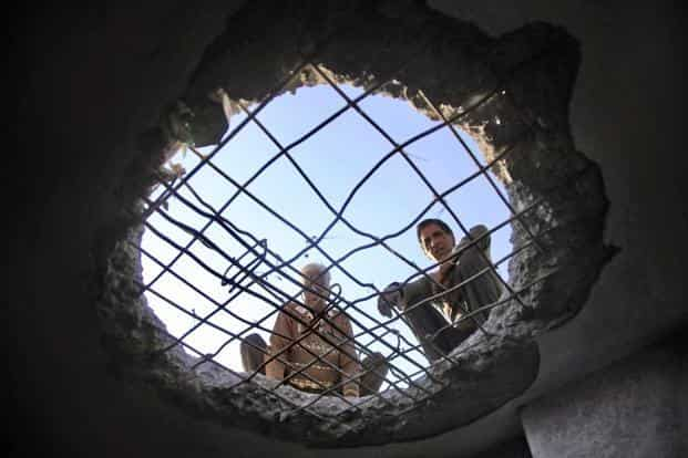 File photo: Villagers look through roof of a house allegedly damaged by shelling from Pakistani side at Nowshera. An official said there was no casualty in the firing in Manjakot and Balakote sectors on Sunday. Pic: PTI