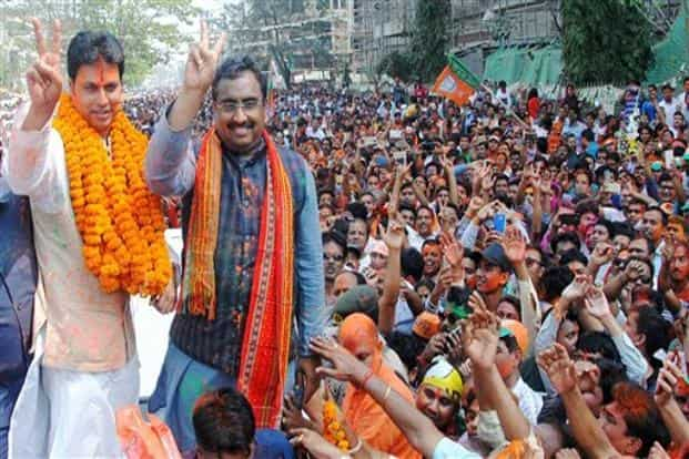 Bharatiya Janata Party general secretary Ram Madhav, state BJP chief Biplab Kumar Deb display victory sign as they celebrate with supporters after party's victory in state Assembly elections results in Agartala on Saturday. Photo: PTI