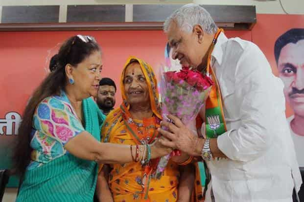 Rajasthan chief minister Vasundhara Raje exchanges a bouquet with NPP leader and MLA Kirori Lal Meena and his wife Golma Devi as they join BJP at BJP office in Jaipur on Sunday. Photo: PTI