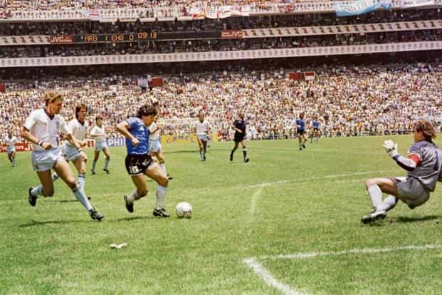 Argentina's Diego Maradona (in blue jersey) runs past English defender Terry Butcher (left) on the way to scoring his second goal during the World Cup 1986 quarter-finals. Photo: AFP