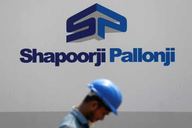 A construction worker walks past a hoarding of Indian conglomerate Shapoorji Pallonji Group on the outskirts of Mumbai on 17 April, 2018. Photo: Reuters