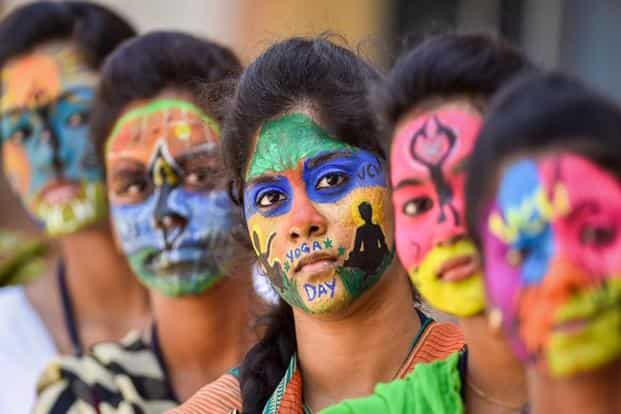 College students with painted faces look on during an event to commemorate International Day of Yoga 2018, in Chennai. Photo: AP