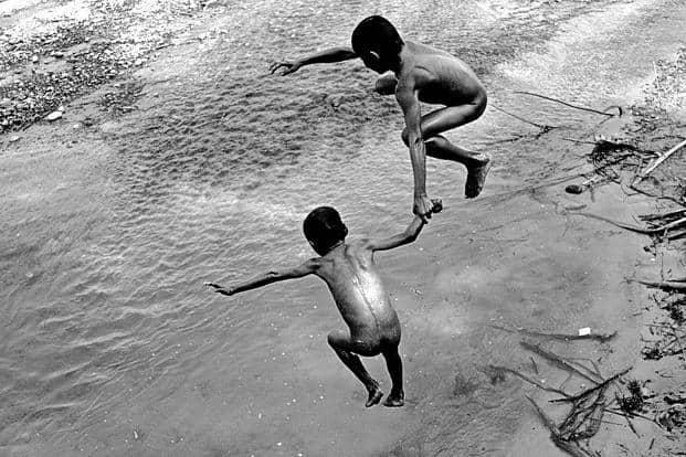 Children dive into the Pandai river at Kairi village. Photo: Eklavya Prasad