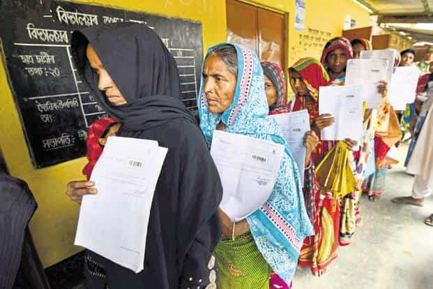Residents hold their documents as they queue up to check their names on the final draft of NRC in Morigoan district of Assam. Photo: AFP