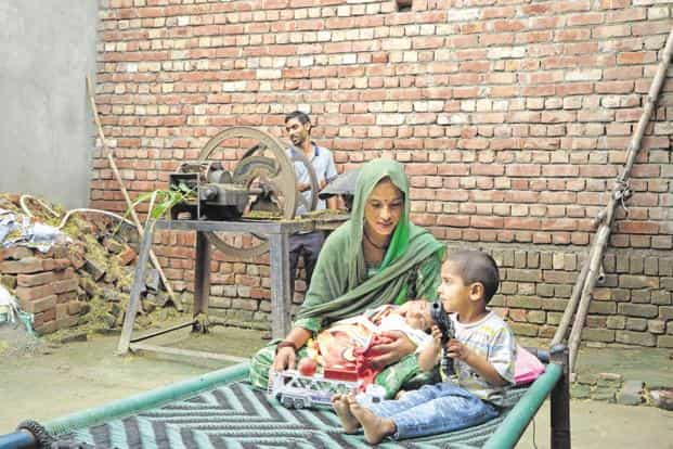Amit Kumar (in the background) and Mausami with their newborn Karishma at their home in Haryana's Indri. They are the first beneficiaries of Ayushman Bharat. Photo: Hemant Rawat/Mint
