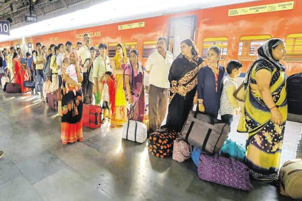 Migrant workers wait to board a train out of Gujarat, in Ahmedabad on Tuesday. Photo: PTI