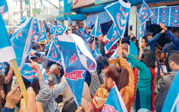 Mizo National Front workers hold their party flag as they celebrate the party's victory in the states Assembly elections. Photo: PTI