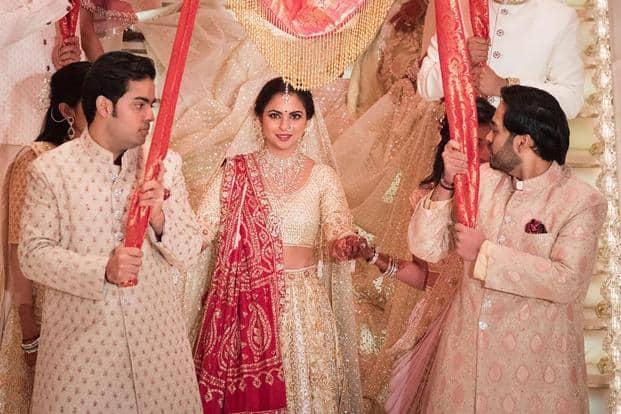 Reliance Industries chairman Mukesh Ambani's sons Akash (L) and Anant (R) taking part in a traditional wedding ritual of their sister Isha Ambani (C) to businessman Ajay Piramal's son, Anand Piramal, in Mumbai.