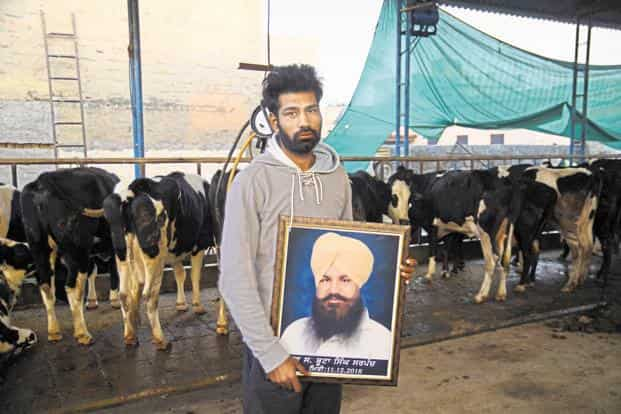 Jagdeep Singh with a photo of his father, who committed suicide on 11 December, at Sangatpura village in Patiala. Photo: Sayantan Bera/Mint